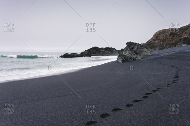 Footsteps left in the black sand beach of Shelter Cove, CA