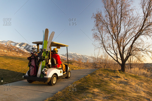 People on electric cart with skis at golf course