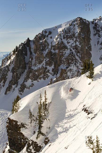 Extreme skier skiing down slope in extreme mountain terrain