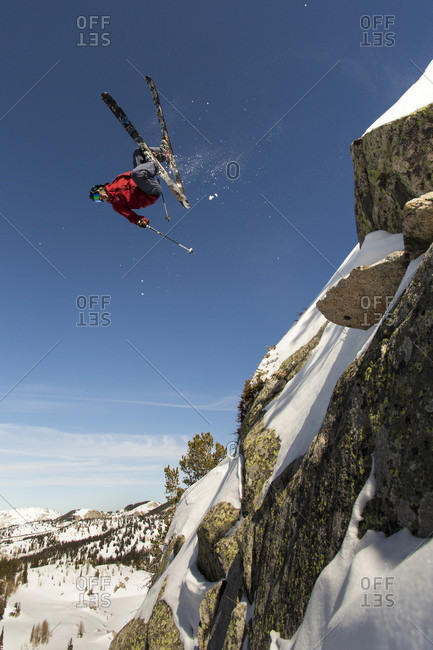 Extreme skier doing upside down stunt jump from cliff