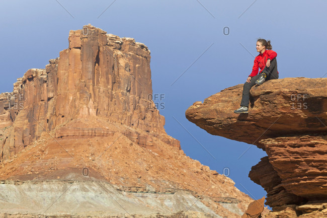 A woman sits on a bedrock terrace at Saddle Horse Bottom below tall canyon walls in Canyon lands National Park, Utah.