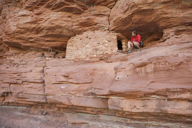 A woman visits a small ruin at the mouth of Jasper Canyon, Canyon lands National Park, Utah.