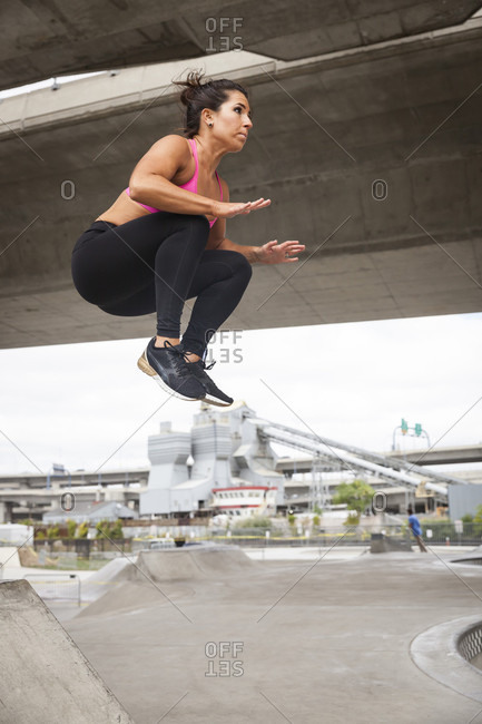 Fit Woman In Workout Clothes Doing A Tuck Jump In The City
