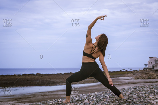 Beautiful Young Woman In Reverse Warrior Pose Doing Yoga At Sunset
