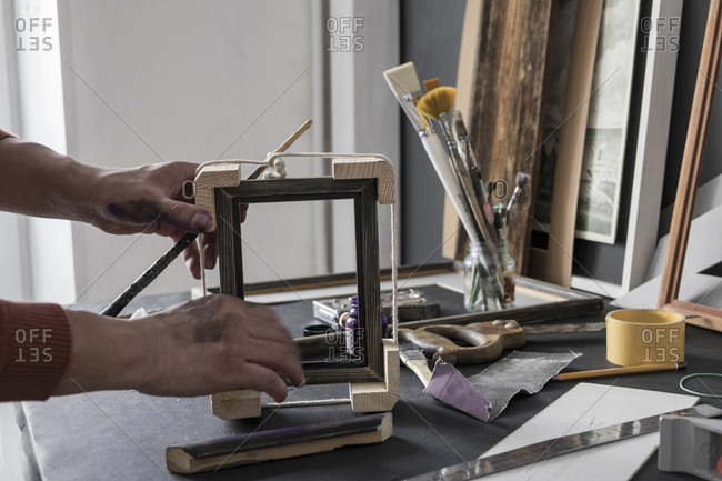 Hands of Caucasian artist making picture frame