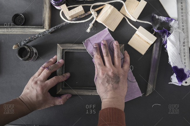 Hands of Caucasian artist sanding picture frame