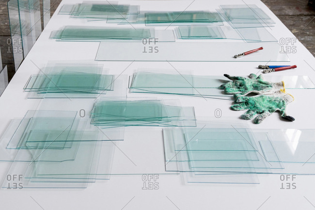 Piles of glass and glass cutter on white table