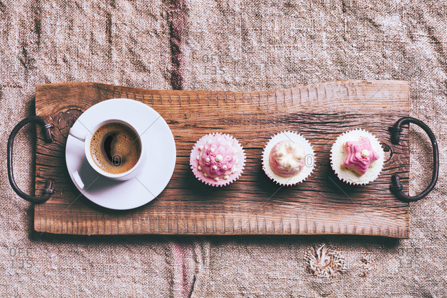 Coffee and cupcakes on wooden tray