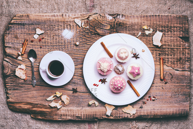 Cupcakes on ingredients on wooden tray with coffee