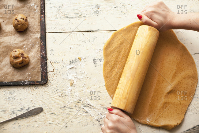 Hands of woman using rolling pin on cookie dough