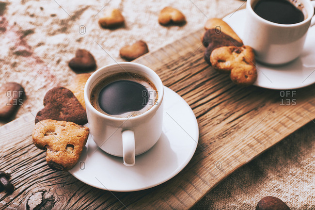 Coffee and heart-shape cookies on wooden tray