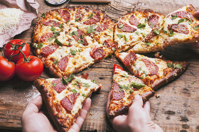 Hands pulling slices of heart-shaped pizza near ingredients on cutting board