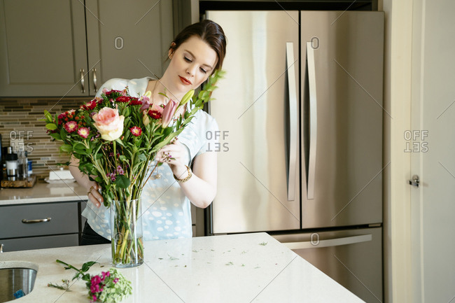 Woman arranging flowers in domestic kitchen