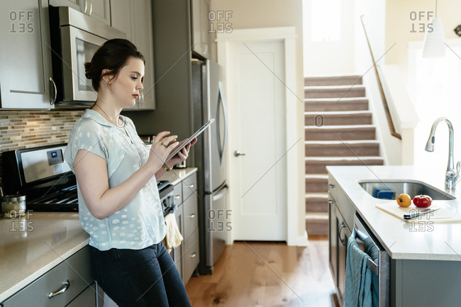 Woman using digital tablet in domestic kitchen