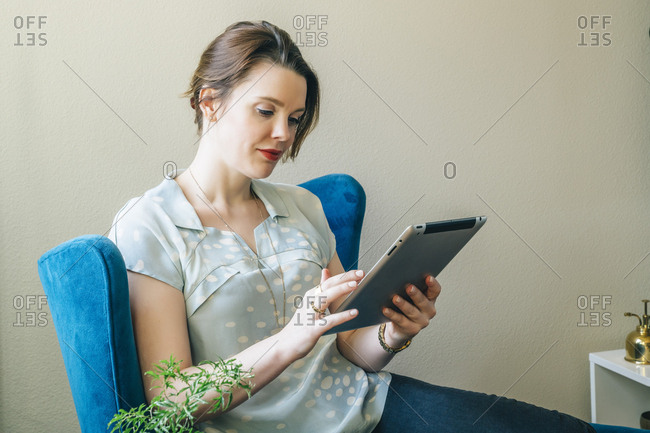 Woman sitting in armchair using digital tablet