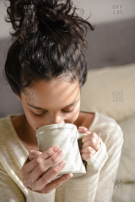 Hispanic woman drinking coffee