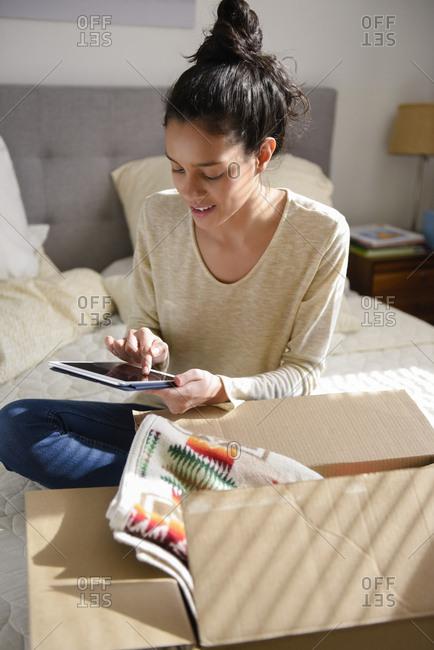 Hispanic woman sitting on bed near box using digital tablet