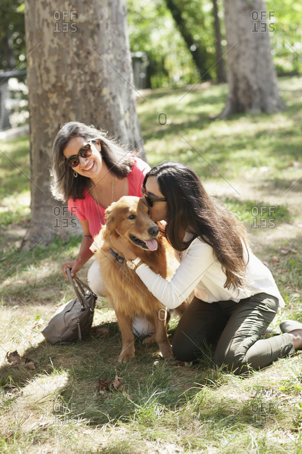 Mother and daughter with pet dog in park