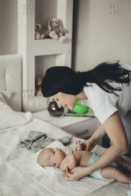Caucasian mother changing diaper of baby son on bed