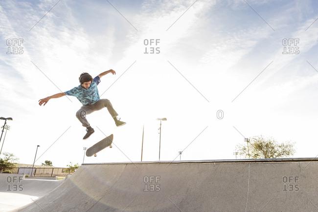 Hispanic man performing mid-air trick on skateboard