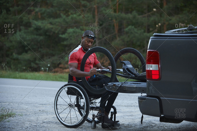 African American man in wheelchair removing hand cycle from truck