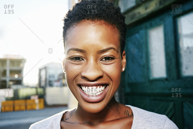 Portrait of smiling Black woman posing in city