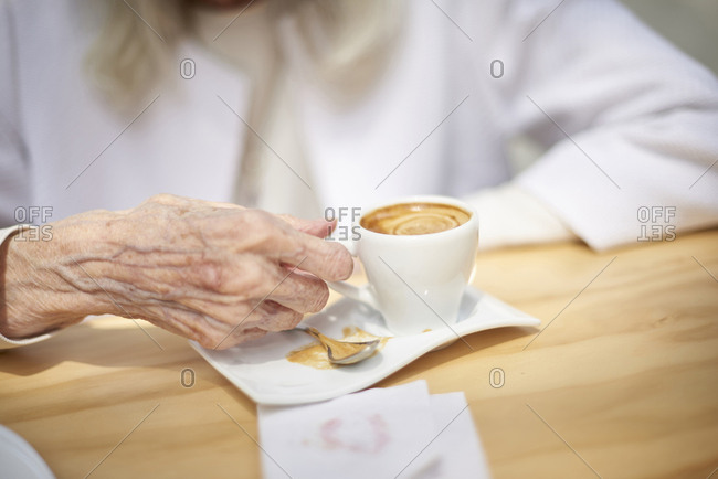 Hand of older Caucasian woman drinking coffee
