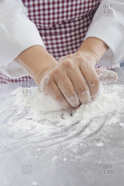 Hands of Hispanic woman kneading dough in flour