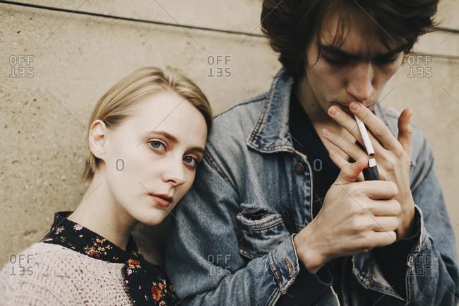 Caucasian man lighting cigarette near woman