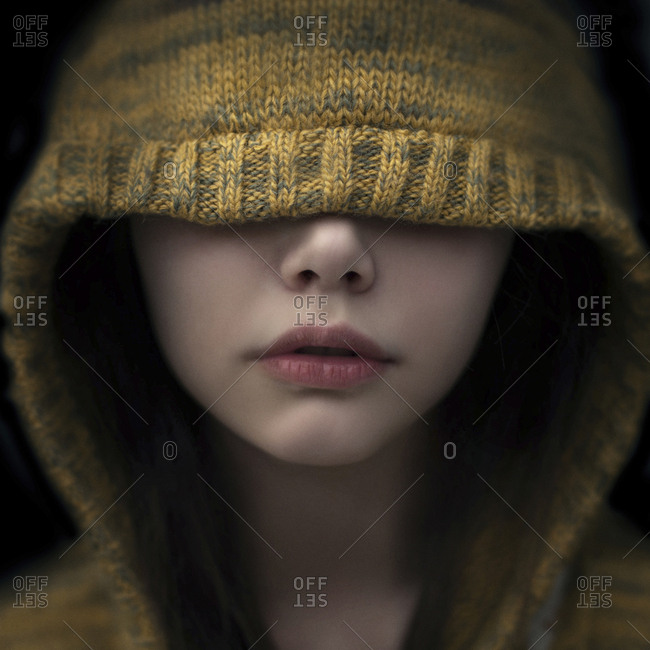 Portrait of Caucasian girl covering eyes with hood