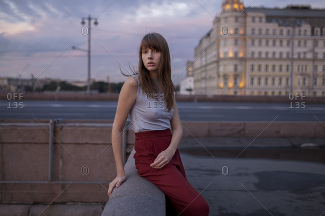 Serious Caucasian woman sitting on wall in city