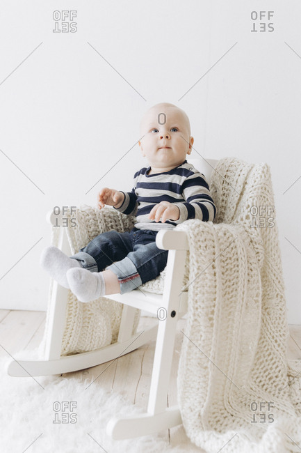 Curious Caucasian baby boy sitting in chair