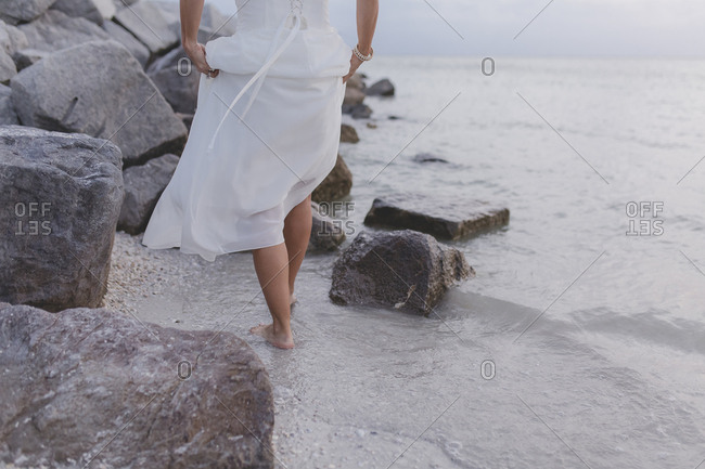 Bride walking along the beach near rocks