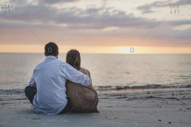 Couple sitting on the beach watching the sunset