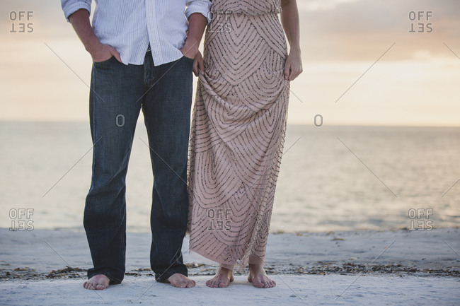 Man and woman dressed up on the beach at sunset