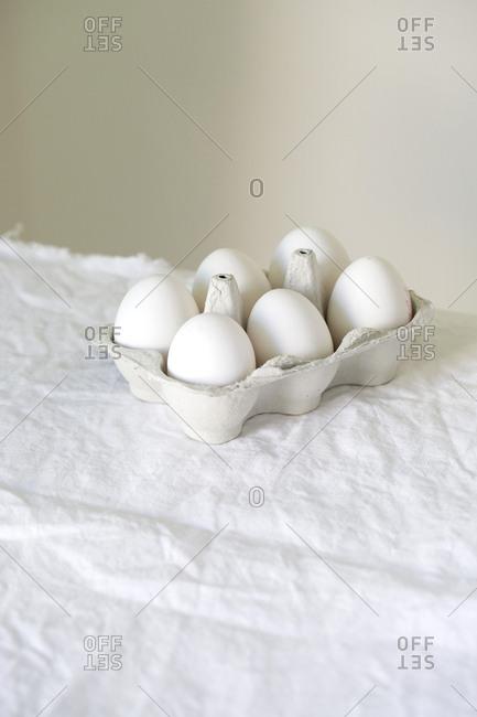 Six white eggs in cardboard carton