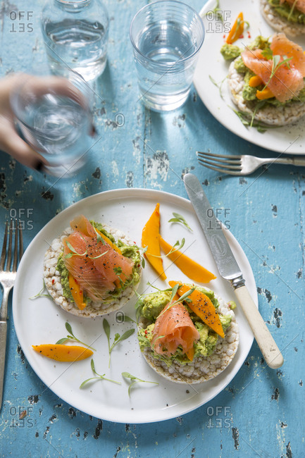 Fresh mango on rice cakes with smoked salmon and avocado