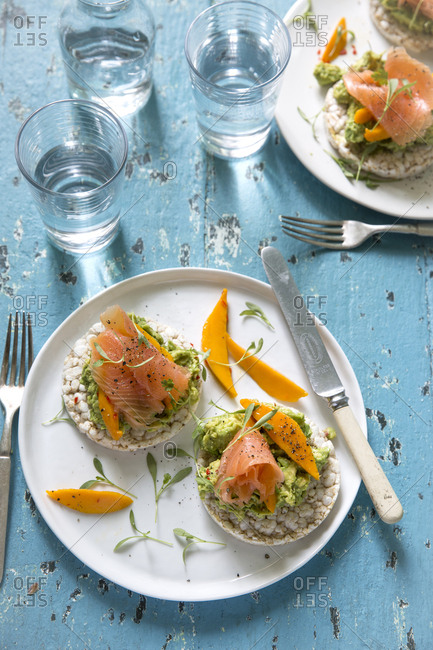 Smoked salmon with avocado and mango on rice cakes