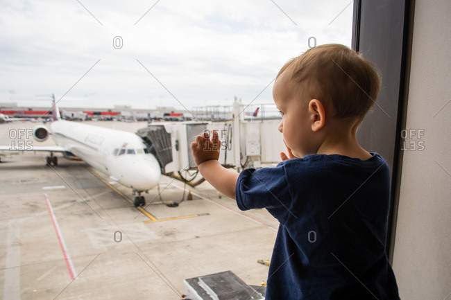 Toddler boy looking out window at airport
