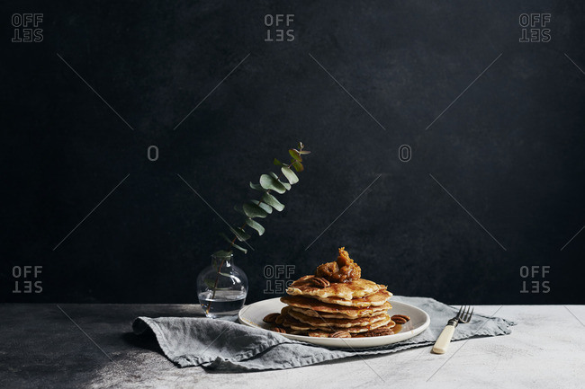 Stack of pancakes with pumpkin butter, pecans and maple syrup