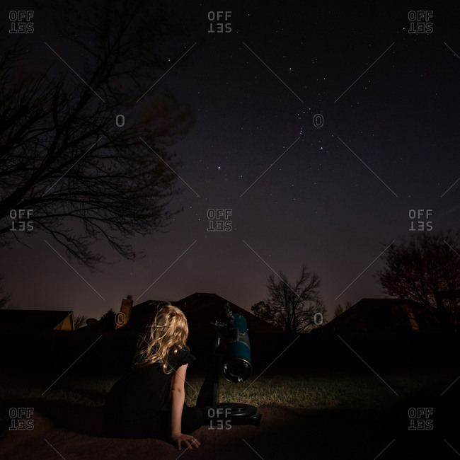 Girl sitting outdoors at night with telescope