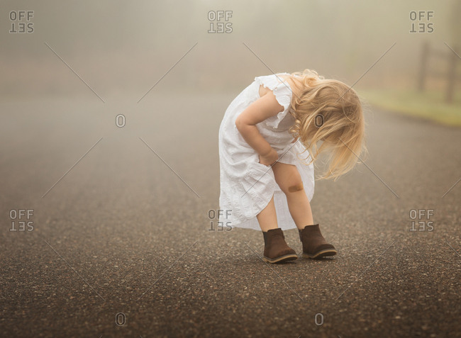 Little girl looking at bandage on knee