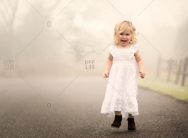 Sad girl outside on a foggy day