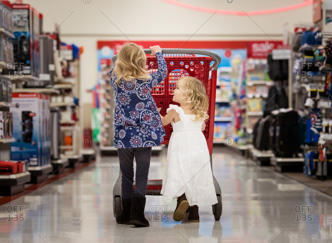Two little girls pushing a shopping cart in a store