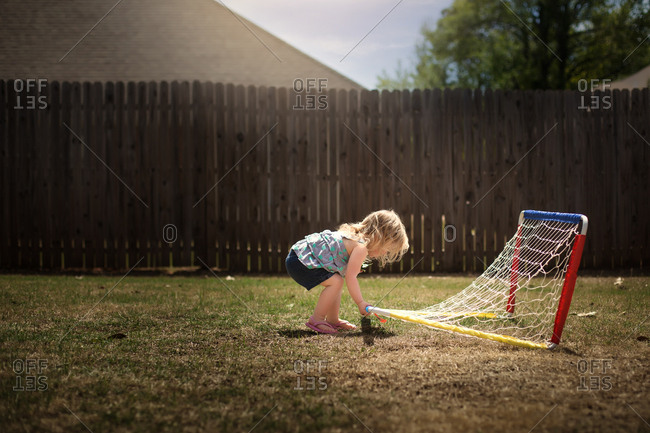Toddler girl playing with sports net in her back
