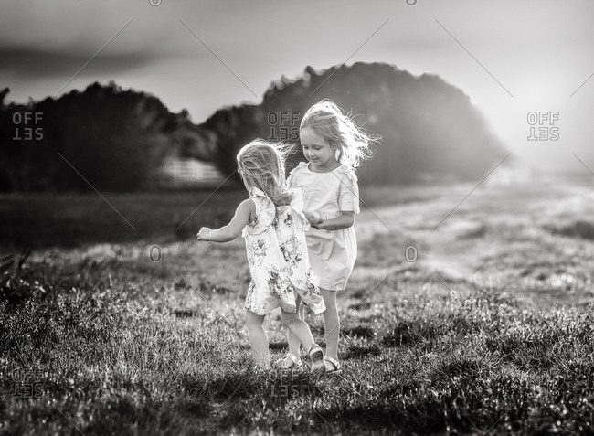 Two girls playing in a field in black and white