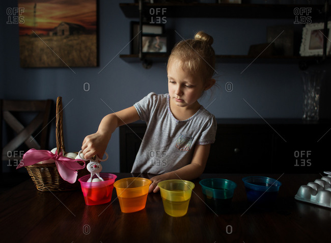 Little girl dying Easter eggs with bunny tongs