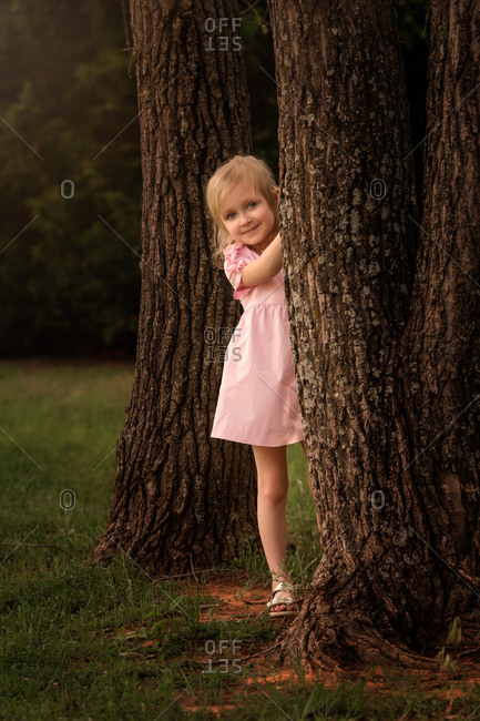 Happy girl peeking out from behind a tree