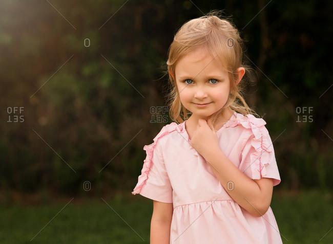 Portrait of a little blond girl in a pink dress