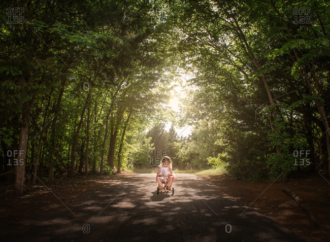 Toddler girl riding tricycle on country road